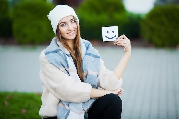 재미있는 미소와 함께 카드를 들고 아름 다운 여자