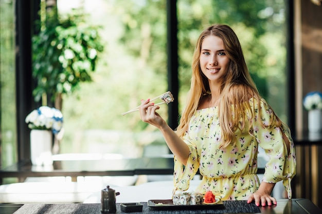 寿司と箸を持っている美しい女性。