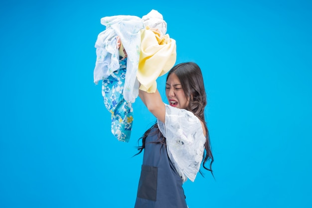 A beautiful woman holding a cloth prepared to wash on blue