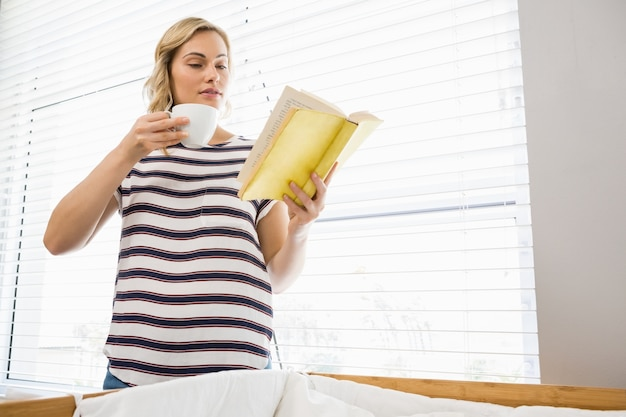 Bella donna che tiene tazza di caffè e leggere il libro
