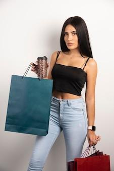 Bella donna che tiene caffè e borse della spesa. foto di alta qualità