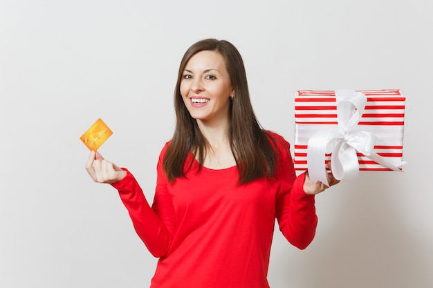 Beautiful woman holding credit card, red present box with gift isolated on white background. for advertisement. st. valentine's day, international women's day, christmas, birthday, holiday concept.