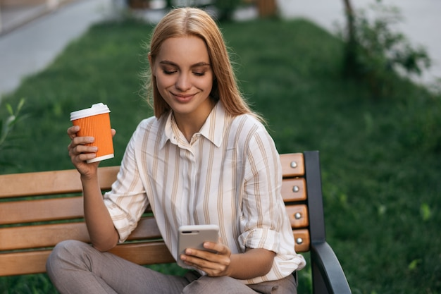Beautiful woman holding cup of coffee, using cellphone