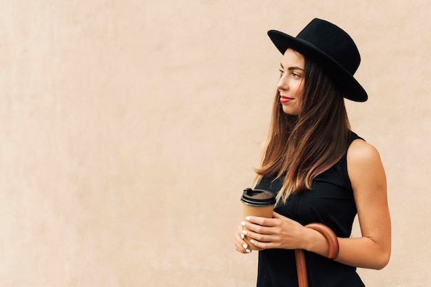 Beautiful woman holding a cup of coffee with copy space