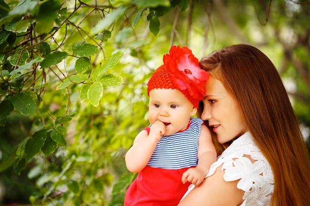 Beautiful woman holding cute curious toddler baby