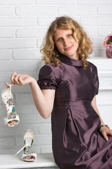ファッショナブルなハイヒールの靴を保持している美しい女性