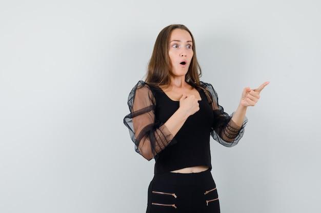 Bella donna che tiene il pugno sul petto mentre indica da parte in camicetta nera e sembra sorpresa