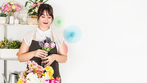 Beautiful woman holding fresh flower vase in floral shop