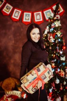 Bella donna azienda regalo su sfondo interni di capodanno