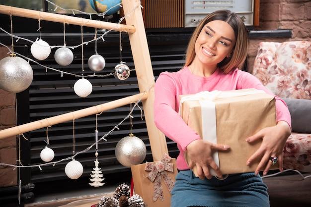 집에서 선물 상자를 들고 있는 아름다운 여자