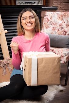 Bella donna che tiene una confezione regalo a casa