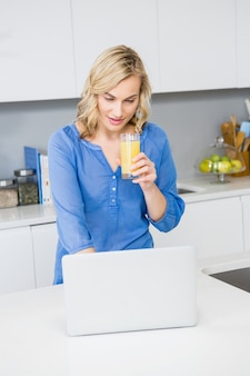 Beautiful woman holding a glass of juice using laptop in kitchen