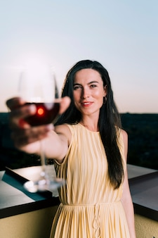 Beautiful woman holding glass of wine blurred foreground