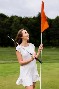 Beautiful woman holding golf pole