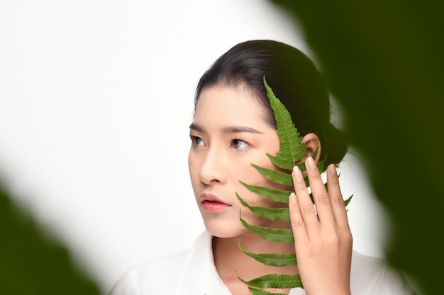 Beautiful woman holding green plant.