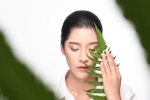 Beautiful woman holding green plant.