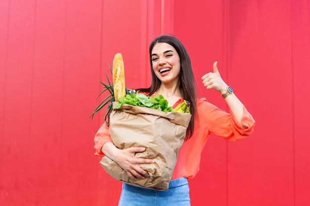 Beautiful woman holding grocery shopping bags on red background showing thumbs up.