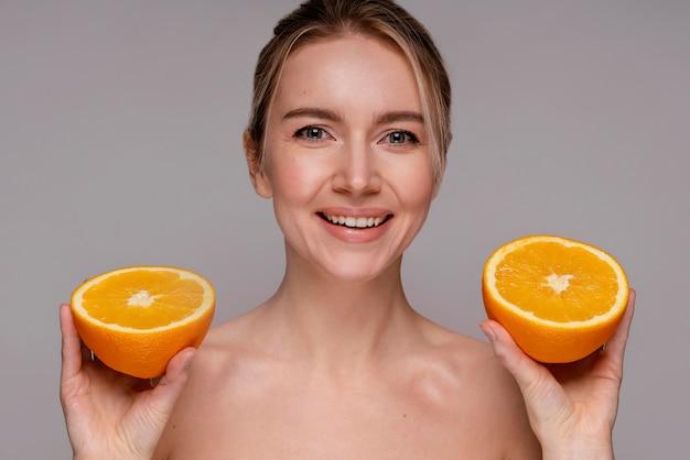 등분 된 오렌지를 들고 아름 다운 여자