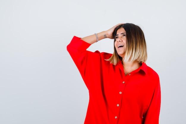Bella donna che tiene la mano sulla testa, distoglie lo sguardo in camicetta rossa e sembra felice, vista frontale.