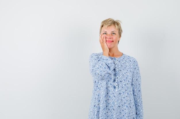 Красивая женщина, держащая руку на щеке в узорной блузке и приятный вид спереди. место для текста