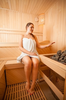 Beautiful woman holding hand over oven at sauna