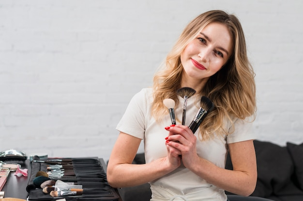 Beautiful woman holding heap of cosmetic brushes
