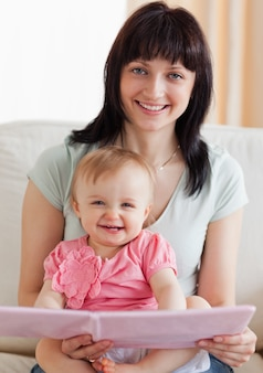 Beautiful woman holding her baby and a book in her arms while sitting on a sofa