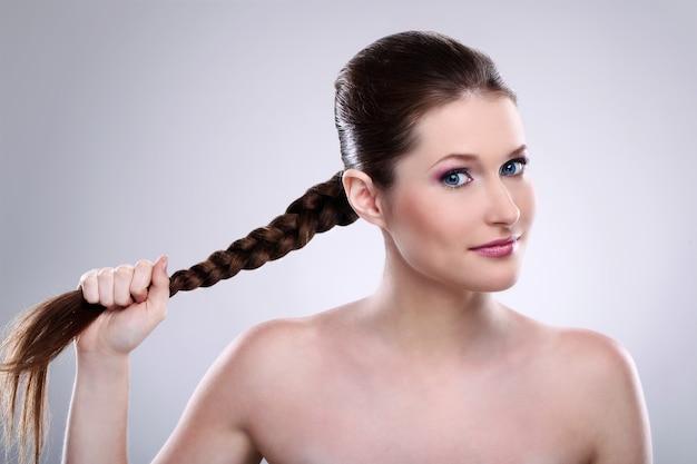 Beautiful woman holding her braid