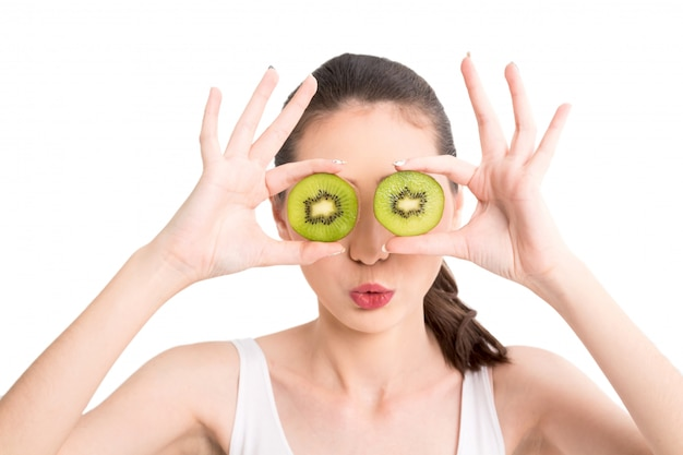 Beautiful woman holding kiwi slice hiding eye behind isolated on white background