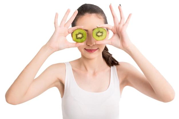 Beautiful woman holding kiwi slice hiding eye behind on white background