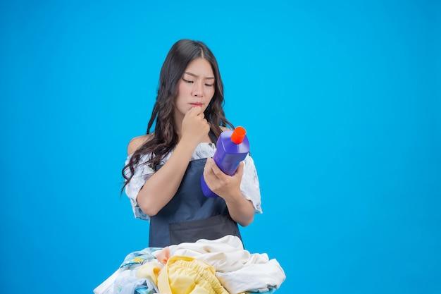 Красивая женщина, держащая стиральный порошок, подготовленный на синем
