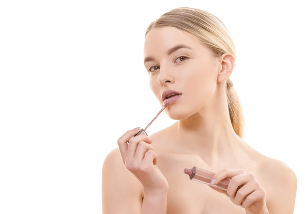 The beautiful woman holding a lip gloss on the white background