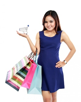 Beautiful woman holding many shopping bags and shopping chart