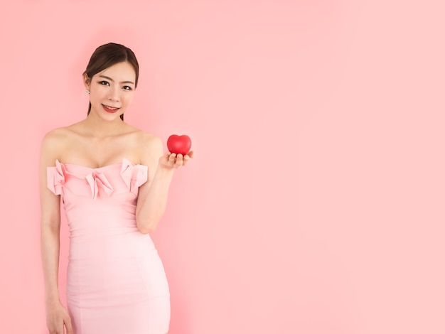 ミニハートを手に持つ美しい女性、ファッションの女の子、ピンクの背景