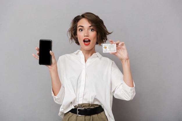 携帯電話とクレジットカードを保持している美しい女性、灰色の壁に隔離