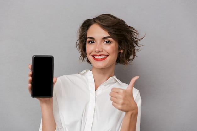 携帯電話を保持し、灰色の壁に隔離されたコピースペース画面を表示している美しい女性