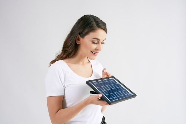 Beautiful woman holding a model of solar panel