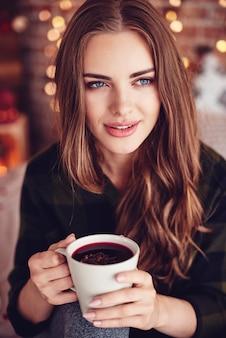 Bella donna che tiene una tazza di vin brulè con lo zenzero