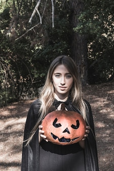 Beautiful woman holding pumpkin in forest