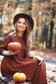 Bella donna che tiene le zucche nei boschi autunnali