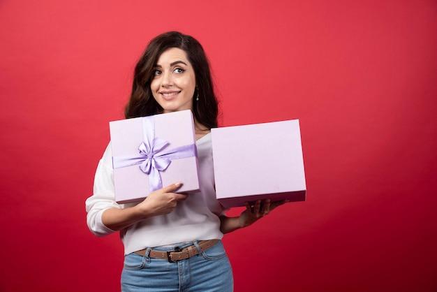 Bella donna che tiene presente viola su sfondo rosso. foto di alta qualità