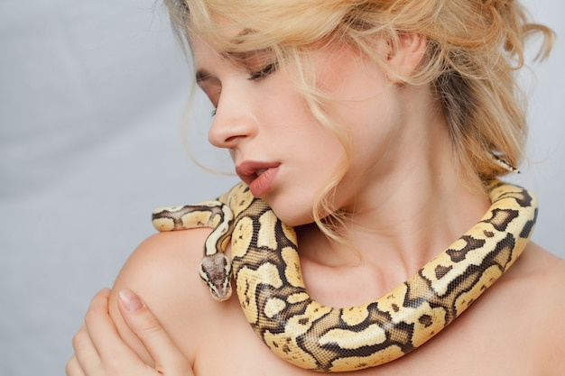 Beautiful woman holding a python, which wraps around her body