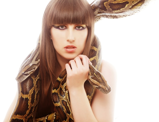 Beautiful woman holding python over white background