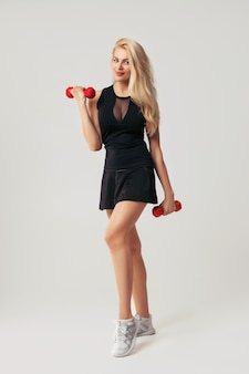 Beautiful woman holding red dumbell