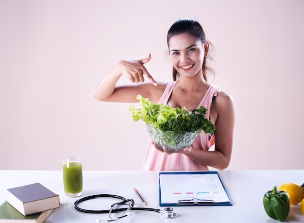 The beautiful woman holding salad bowl in hand , show fresh vegetable, good for diet, blurry light around