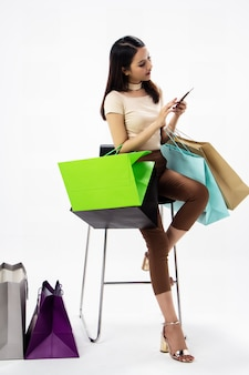 The beautiful woman holding shopping bags in hand, using mobile phone for shopping online