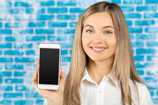 Beautiful woman holding and showing white mobile phone with blank black screen