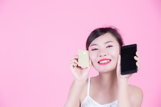 Beautiful woman holding a smartphone and card on a pink background