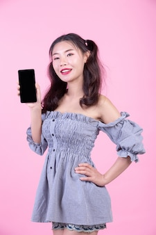 Beautiful woman holding a smartphone on a pink background.