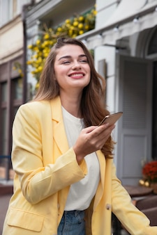 Beautiful woman holding smartphone while being on a bike